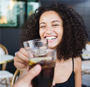 A smiling woman cheersing a beverage